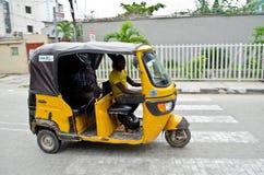 Chaufförer av gula tuktuks ply deras handel runt om hamnstaden Royaltyfri Bild