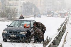 Chaufförer försöker att installera kedjor på deras däck under skurkroll fotografering för bildbyråer