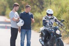 Chaufförinstruktören kontrollerar mopedpiloten royaltyfri fotografi