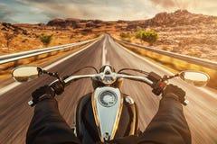 Chaufförridningmotorcykel på asfaltvägen arkivfoto