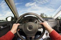 Chaufförs händer på styrninghjulet royaltyfri foto