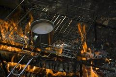Chauffage d'une tasse de café tout en brûlant un feu dans un terrain de camping sauvage image libre de droits