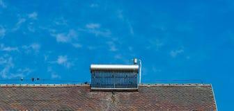 Chauffe-eau solaire sur le vieux dessus de toit, oiseaux, excréments d'oiseaux sur le chauffe-eau photographie stock libre de droits
