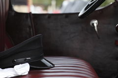 Chauffer hat and gloves. On the seat of a classic car Royalty Free Stock Photography