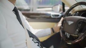 Chauffer personal en el traje de negocios que conduce el coche de lujo, servicio costoso metrajes