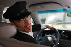 Chauffeur. Portrait of a handsome male chauffeur sitting in a car talking to passenger Stock Photography
