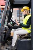 Chauffeur de camion femelle de chariot élévateur en dehors d'un entrepôt photos libres de droits