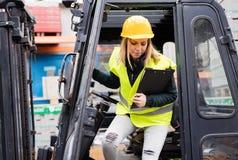 Chauffeur de camion femelle de chariot élévateur en dehors d'un entrepôt Photographie stock libre de droits