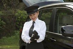 Chauffeur die op haar drijfhandschoenen zetten stock fotografie