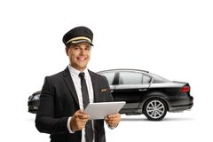 Chauffeur with a digital tablet standing in front of a black car. Isolated on white background