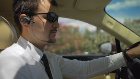 Chauffeur of elite taxi driving car in resort town and talking to passenger. Stock footage stock video