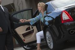 Chauffeur Helps Woman Get Down From Car Stock Photography