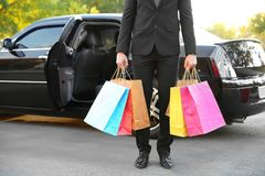 Chauffeur holding colourful packs and standing near luxury. Car, closeup Stock Photo