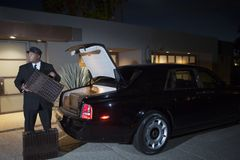 Chauffeur Loading Suitcases In Car. Chauffeur loads suitcases into luxury car at night Stock Photography