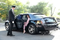 Chauffeur opening car door. For businesswoman Stock Photos