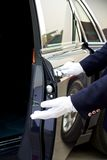 Chauffeur opens car door. Of a rolls royce Stock Image