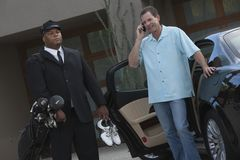 Chauffeur With Owner Standing By Car stock photo