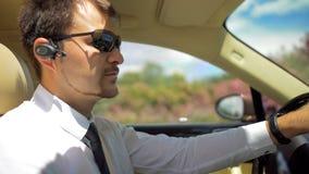 Chauffeur professionnel de taxi d'élite conduisant la voiture, écoutant le casque de bluetooth Photo stock
