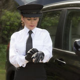 Chauffeur putting on her driving gloves Royalty Free Stock Images