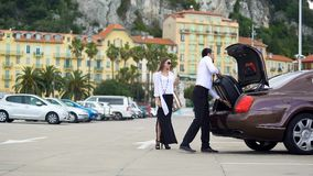 Chauffeur putting luggage in trunk, elite car service for business people. Stock footage Stock Photos