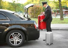 Chauffeur putting suitcase. In car trunk Stock Photos