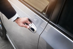 Chauffeur s hand on handle. Close-up of man in formal wear openi Stock Photography