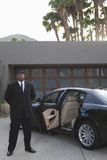 Chauffeur Standing By Car. Full length of a mixed race chauffeur standing by an open door of car on driveway outside house Royalty Free Stock Images
