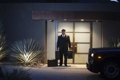 Chauffeur Stands At Lit Entrance Doorway With Luggage. Full length of chauffeur stands at lit entrance doorway with luggage Stock Photo