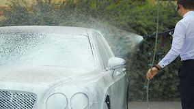 Chauffeur washing luxury automobile with suds, responsible work, business. Stock footage stock video footage