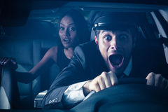 Chauffeur with woman gets into car crash. Male chauffeur with women on back seat gets into car crash and makes ridiculous face Royalty Free Stock Photography