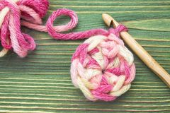 Chauffez la boule rose de fil d'hiver pour tricoter et faites du crochet sur la table en bois Photo de plan rapproché de napperon Photo libre de droits