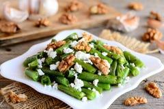 Chauffez la salade de haricots verts avec le fromage blanc et les noix d'un plat blanc et d'une vieille table en bois Type rustiq image stock