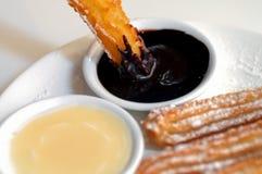 Chauffez le beignet espagnol de churros plongeant à la crème au chocolat foncée Photographie stock