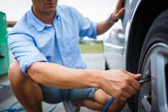 Chaufför som kontrollerar luft för lufttryck och fyllningi gummihjulen Royaltyfri Foto