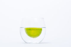 Chaulez le flottement dans un verre de l'eau d'isolement Photographie stock libre de droits