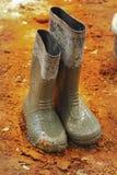 Chausse les bottes en caoutchouc au sol. Image libre de droits