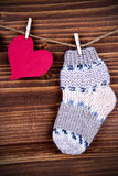 Chaussette de bébé avec le coeur rouge sur le bois Photo libre de droits