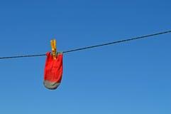 Chaussette rouge sur la ligne de lavage d'A Photographie stock libre de droits
