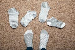 Chaussettes avec différents modèles dispersés sur le plancher dans la maison, choix images libres de droits