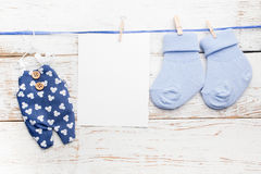 Chaussettes bleues de petit garçon, carte vierge et combinaisons sur le fond en bois blanc Configuration plate Photographie stock libre de droits