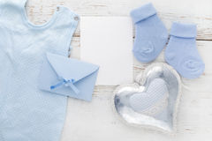 Chaussettes bleues de petit garçon, carte vierge, evelop et coeur sur le fond en bois blanc Configuration plate Photo stock