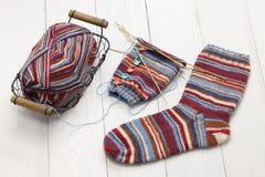Chaussettes d'hiver, boule de fil et aiguilles de tricotage chaudes de tricotage Photo stock