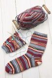 Chaussettes d'hiver, boule de fil et aiguilles de tricotage chaudes de tricotage Photos stock