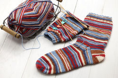 Chaussettes d'hiver, boule de fil et aiguilles de tricotage chaudes de tricotage Images stock