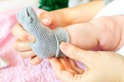 Chaussettes de gris d'usage de bébé Photographie stock