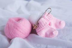 Chaussettes de laine assez roses de bébé sur le fond blanc Images libres de droits