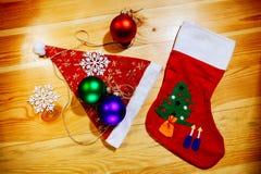 Chaussettes de Noël et chapeau de Santa avec des flocons de neige de boules Image stock