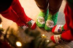 Chaussettes de Noël Trois paires de pied, habillées dans des soks de Noël, se tiennent autour d'un arbre L'atmosphère de Noël images stock