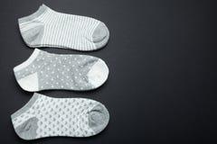 Chaussettes femelles grises sur un fond noir, l'espace pour le texte image libre de droits