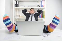 Chaussettes géniales. Homme d'affaires heureux dans les chaussettes géniales se reposant à son wor Photos stock